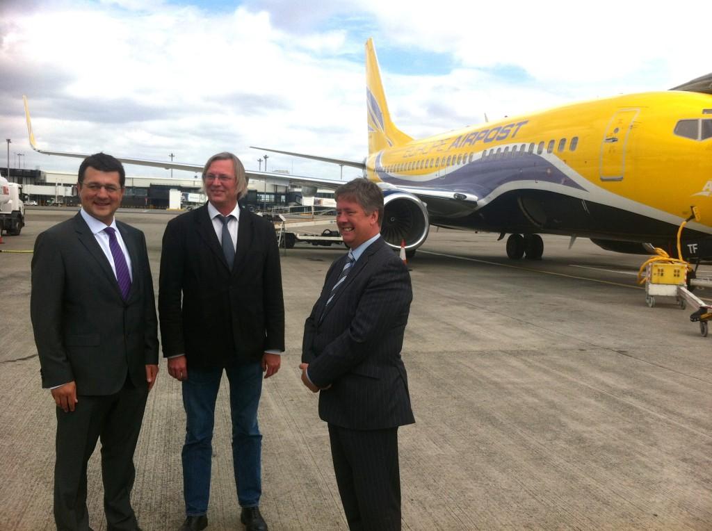 Jean-François Dominiak, directeur général d'Europe Airpost (au centre) accueilli à Glasgow par Keith Brown, ministre des transports écossais (à droite) et François Bourienne, directeur commercial de l'aéroport de Glasgow (à gauche) lors du vol inaugural d'Europe Airpost entre Paris, Glasgow et Halifax le 3 juillet 2014